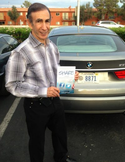 BluBlocker founder Joe Sugarman posing with his copy of Share